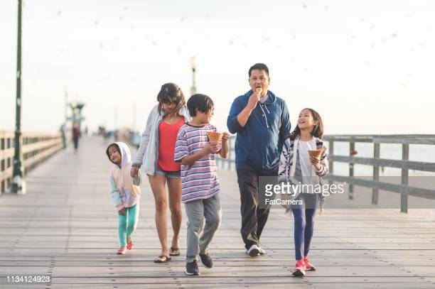 family eating ice cream on a beach boardwalk - pacific ocean stock pictures, royalty-free photos & images