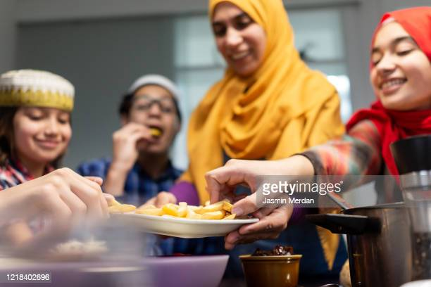 family eating iftar and enjoying breaking of fasting - ベール ストックフォトと画像
