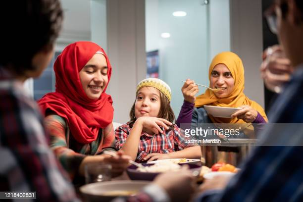 family eating iftar and enjoying breaking of fasting - middle eastern culture stock pictures, royalty-free photos & images