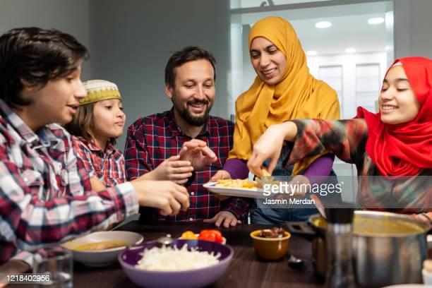 family eating iftar and enjoying breaking of fasting - zurückhaltende kleidung stock-fotos und bilder