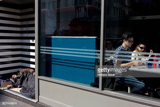 Family eating in restaurant and and sleeping homeless man in central London doorway With a theme of stripes that appear on the window and the walls...