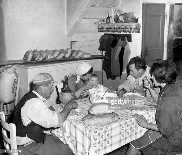 Family eating in the backshop of the bakery bread on the table 1967