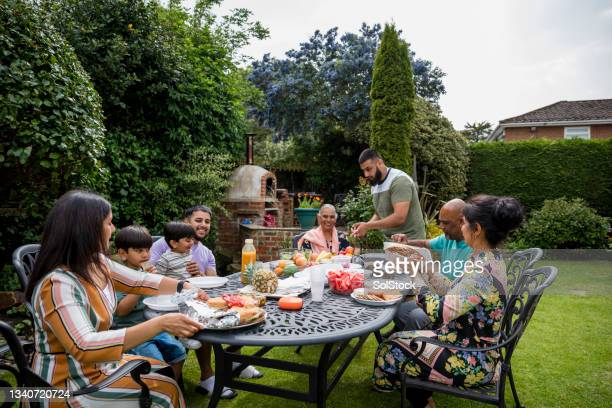 family eating in the sun together - human relationship stock pictures, royalty-free photos & images