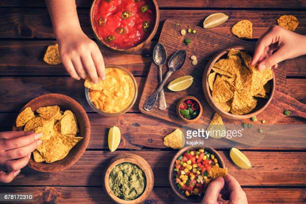 family eating nachos with sauces - cheese sauce stock photos and pictures