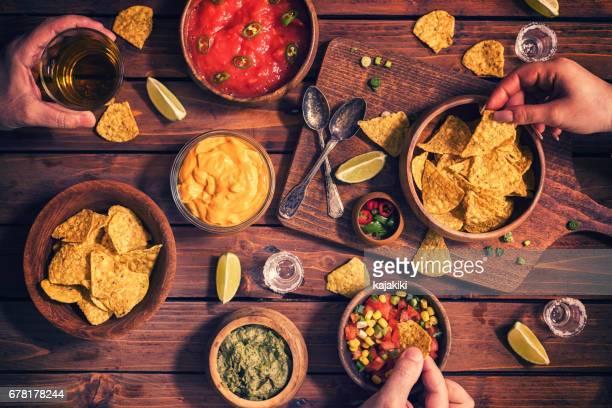 Familie essen Nachos mit Saucen