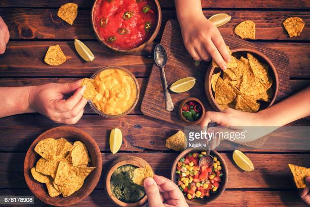 family eating nachos with sauces - nachos stock pictures, royalty-free photos & images