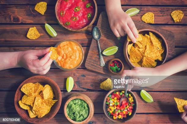 ソースとナチョスを食べて家族 - タレ ストックフォトと画像
