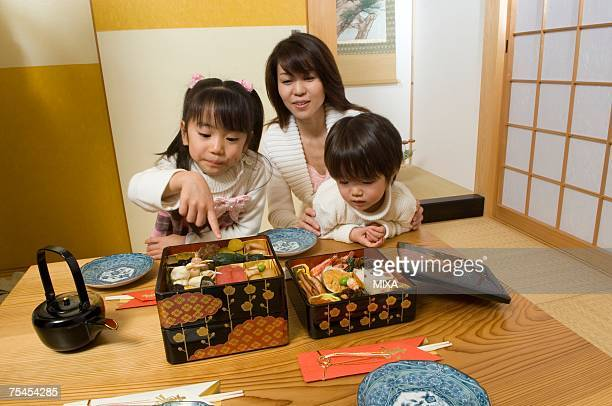 family eating new year's day meal - osechi ryori stock pictures, royalty-free photos & images