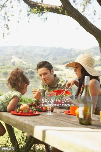 family eating on a picnic table outdoors - maduro fotografías e imágenes de stock