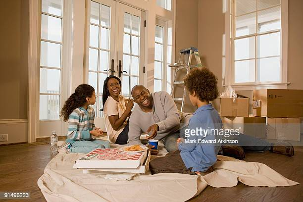 family eating on floor in new home - pizza box stock photos and pictures