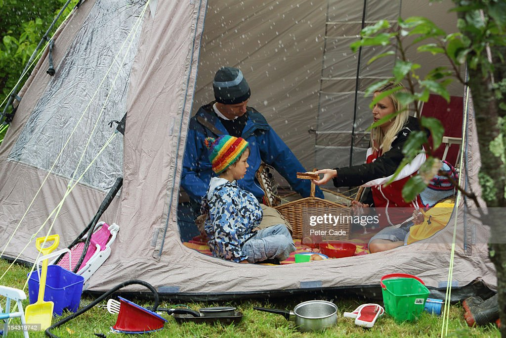 Family eating picnic in tent due to rain  Stock Photo & Family Eating Picnic In Tent Due To Rain Stock Photo | Getty Images