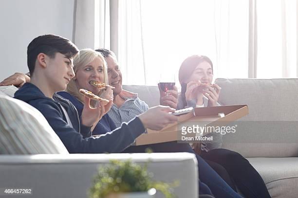 Famille manger pizza et regarder la télévision à la maison