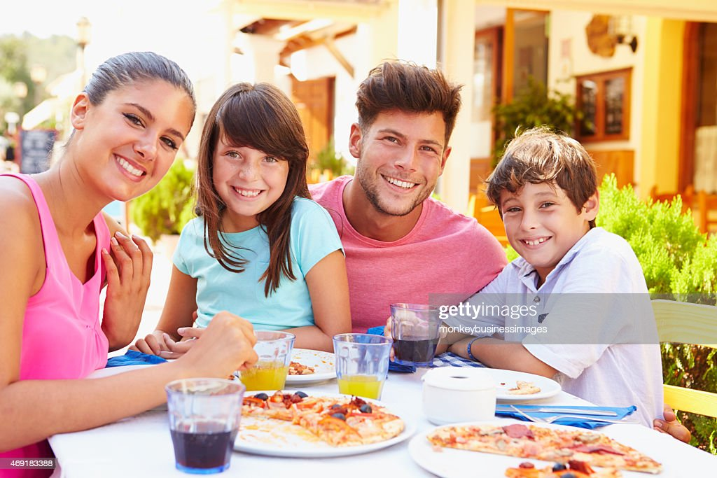 Family eating pizza at outdoor restaurant smiling for camera : Stock Photo