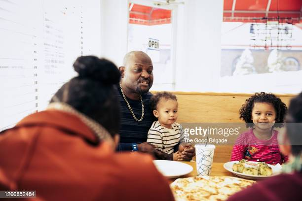 family eating pizza at restaurant - modern manhood stock pictures, royalty-free photos & images
