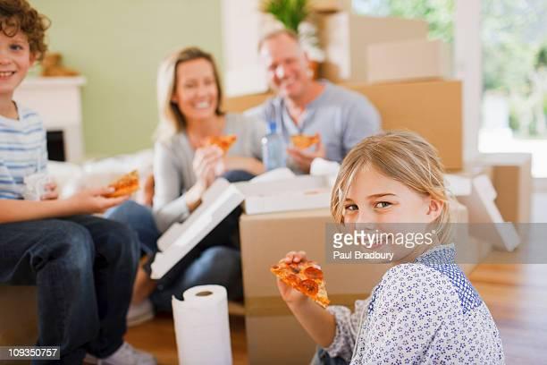 Familie Essen pizza auf dem Boden im neuen Haus