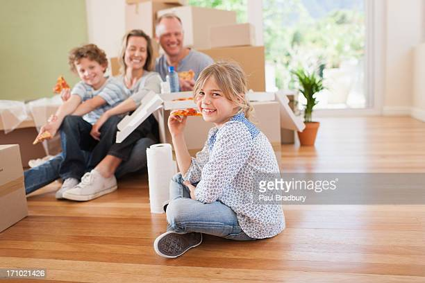 Family eating pizza on the floor in their new house