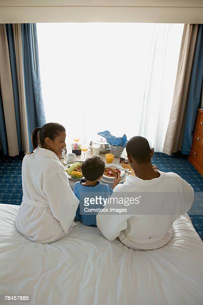 Family eating room service breakfast in hotel room