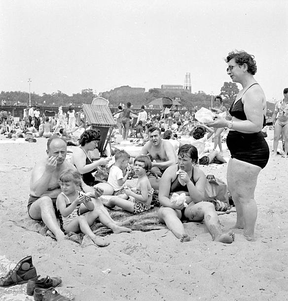 Family eating sandwiches on the beach at Coney Island.
