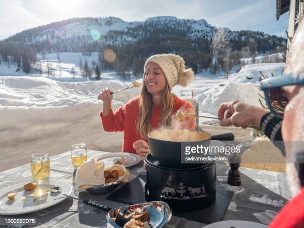 family eating swiss cheese fondue in the alps in winter - swiss culture stock pictures, royalty-free photos & images
