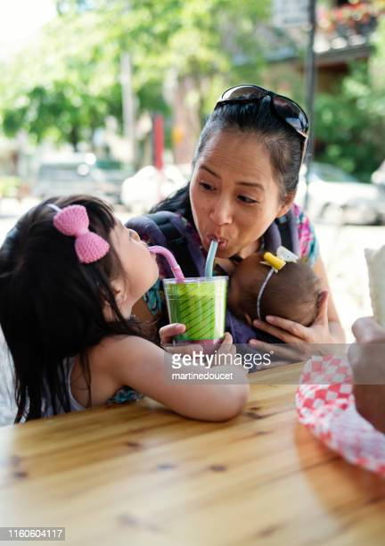 """family eating take out food outdoors. - """"martine doucet"""" or martinedoucet stock pictures, royalty-free photos & images"""