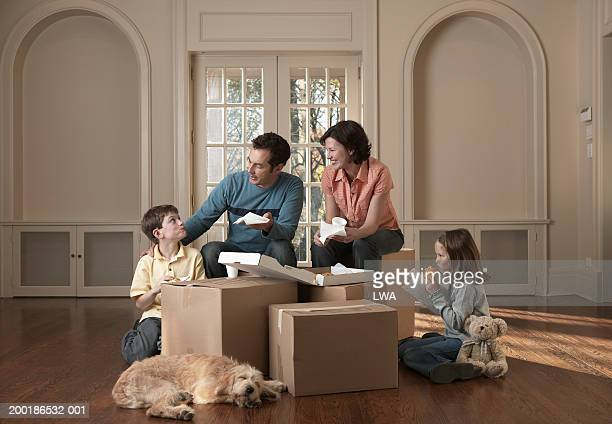 family eating takeout in barren room by cardboard boxes - dog eats out girl stock pictures, royalty-free photos & images
