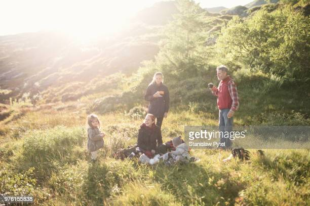 Family eating, taking break when trekking in mountains