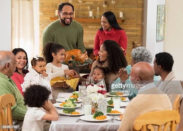 family eating thanksgiving dinner - african american family dinner stock photos and pictures