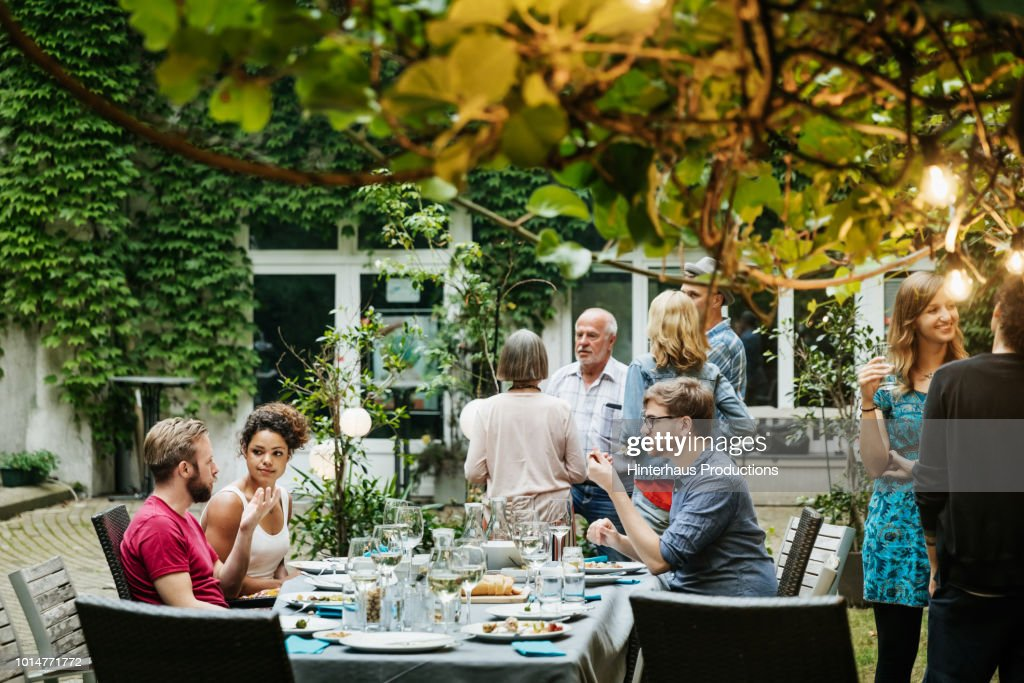 Family Eating together In Courtyard : Stock Photo