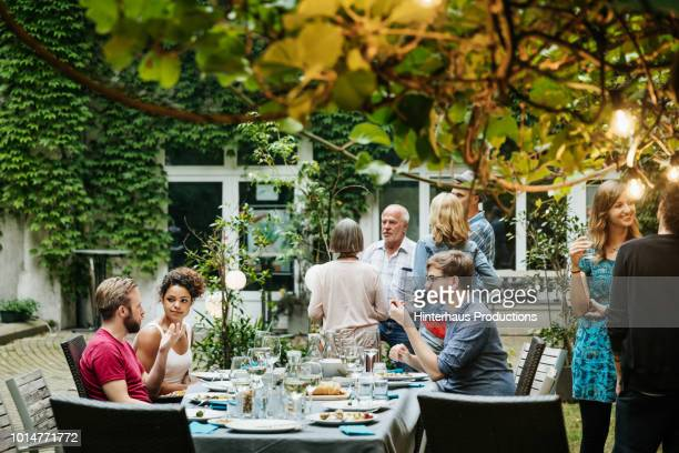 family eating together in courtyard - vie simple photos et images de collection