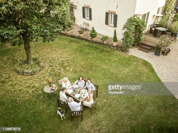 family eating together in the garden in summer - vie simple photos et images de collection