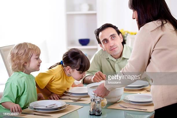 Familia comiendo juntos, madre ofrece sopa en la tabla