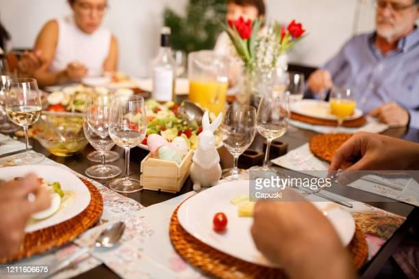 familie essen zusammen auf dem tisch für ostern - ostern stock-fotos und bilder