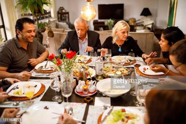 family eating together on table for easter - easter dinner stock pictures, royalty-free photos & images