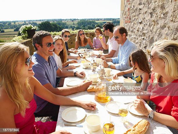 family eating together outdoors - french culture stock pictures, royalty-free photos & images