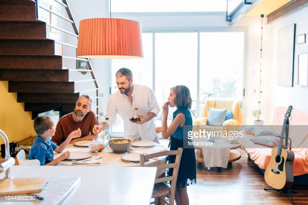 lgbtq family eating together - homosexual stock pictures, royalty-free photos & images