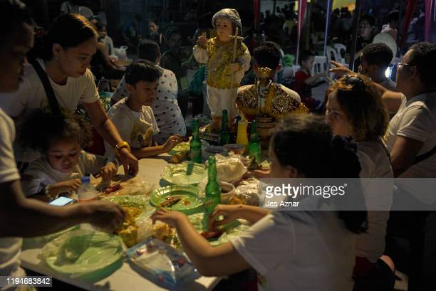 A family eats at an outdoor restaurant with an image of the Holy Child Jesus on the table as they pray and dance as they participatein the annual...