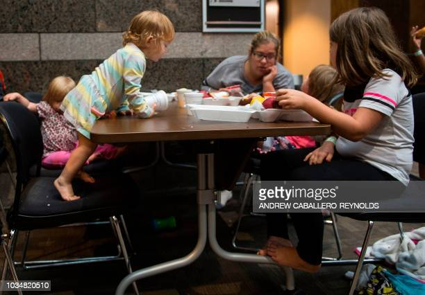 A family eats breakfast inside an American Red Cross evacuation shelter in Chapel Hill North Carolina on September 17 2018 Catastrophic floods raised...