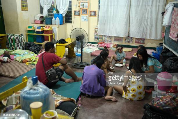 A family eats dinner at a temporary evacuation center at Balzain East Elementary School ahead of Typhoon Mangkhut's arrival in Tuguegarao Cagayan...