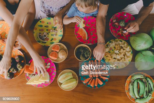 Family eats  tropical fruits on patio