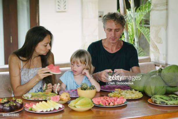 family eats  tropical fruits on patio - expatriate stock pictures, royalty-free photos & images