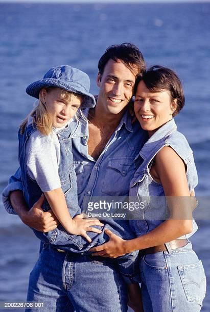 Family embracing at seaside, father holding daughter (8-9 years), portrait