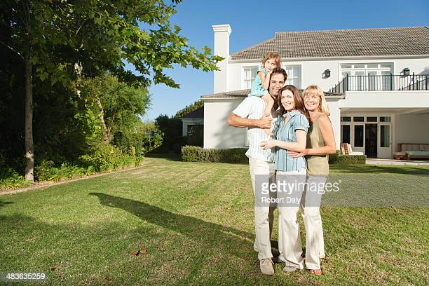 A family embracing in front of a large home