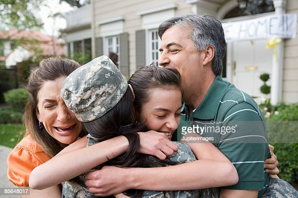 Family embracing soldier