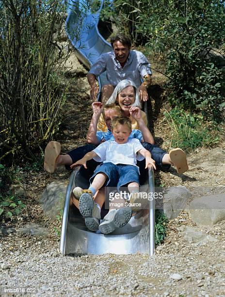 Family enjoy going on a slide.