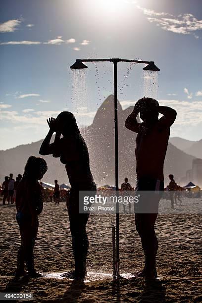Family enjoy refreshing shower at Ipanema beach Rio de Janeiro Brazil