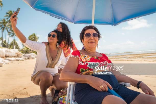 familie genießen das wochenende am strand - mother daughter webcam stock-fotos und bilder