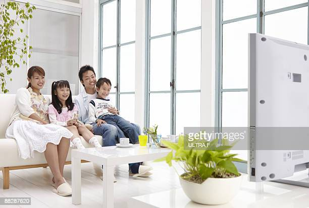 A family enjoy watching TV.