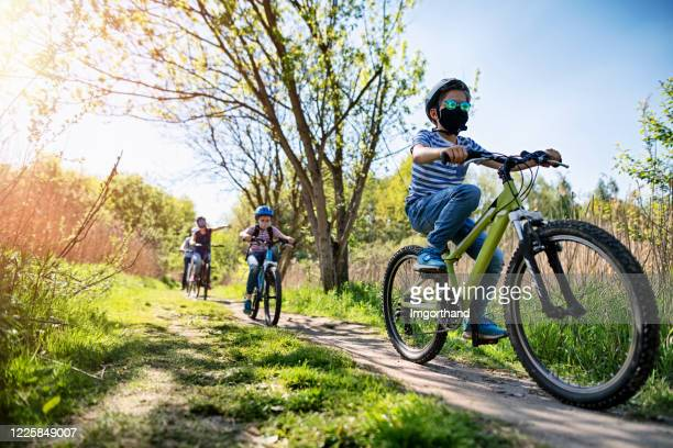 family enjoying a bike trip during covid-19 pandemic - cycling stock pictures, royalty-free photos & images