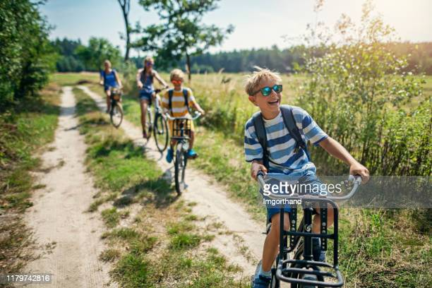 family enjoying a bike trip - rural scene stock pictures, royalty-free photos & images