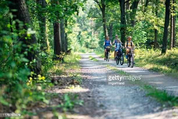 family enjoying a bike trip - woodland stock pictures, royalty-free photos & images